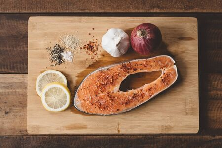 Top view of a fresh uncooked salmon on a wooden cutting board. Concept of diet menu and cooking ingredient