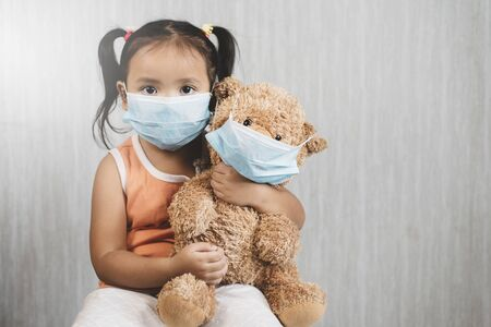 Little asian girl child holding a teddy bear wearing a mask. Concept of pediatric health care and infection