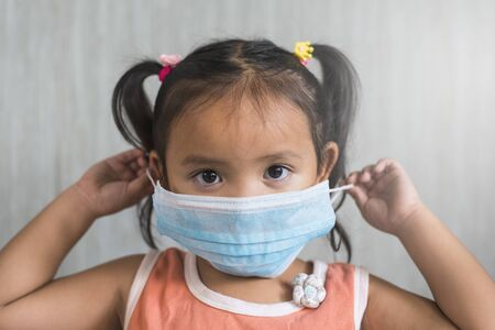 little asian girl wearing a surgical mask. Concept of child heatlh care and infection protection 免版税图像 - 144232250