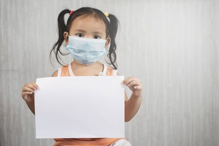 Little asian girl wearing surgical mask while holding blank white paper. Concept of child health care and virus desease outbreak 免版税图像 - 145966449