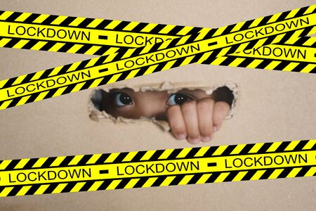 Little girl peeking from a hole on cardboard box with lockdown sign. selective focus on her eye. Concept of lockdown on global crisis