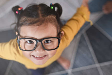 High Angle view of a smiling little asian girl wearing fancy glasses. Concept of happy child and emotions