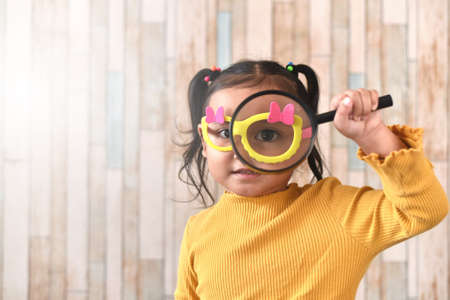 Cute little asian girl looking through a magnifying glass. Concept of curiosity child learning and eyesight