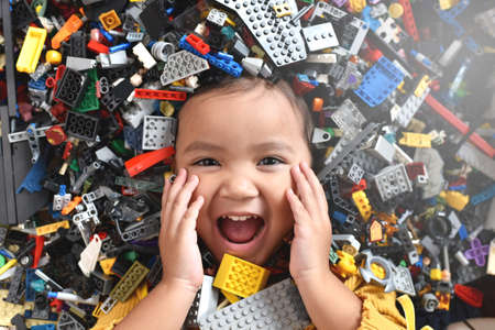 Little asian girl looking at camera surrounded by toy bricks block. Concept of Child development Stock Photo