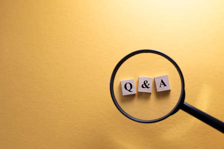 Magnifying glass focus on Q&A wooden alphabet letter. Concept of question and answer