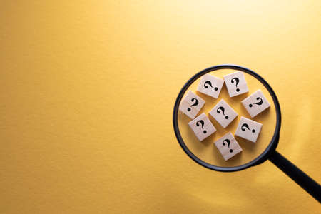Focus on Question Mark symbol on a wooden tiles using magnifying glass against yellow background. Concept of Q and A, questions and faq Stock Photo