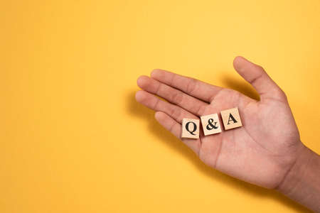 hand showing Q and A wooden alphabet tile. Concept of Questions and Answers support