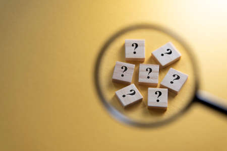 Selective focus on Question Mark symbol on a wooden tiles using magnifying glass against yellow background. Concept of Q and A, questions and faq Stock Photo