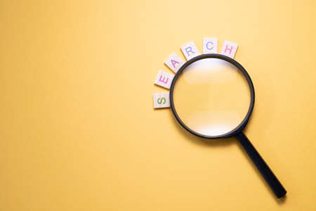 Magnifying glass and wooden alphabet tiles letter SEARCH. Concept of research and finding.