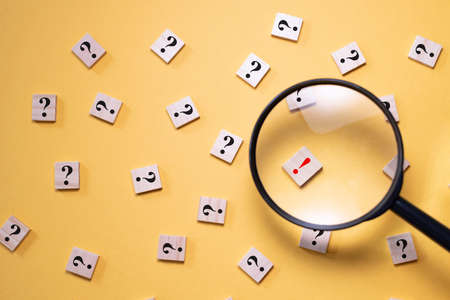 Magnifying glass focus on exclamation mark between question mark. Concept of Q&A, FAQ choice and solution Stock Photo