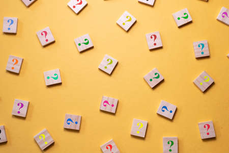 Colorful question mark symbol on wooden tile agains yellow background. Concept of Diversity, FAQ, Q and A and questions Stock Photo