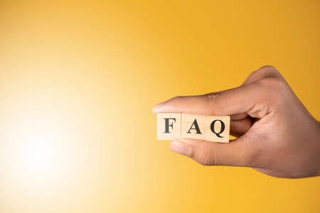 Hand holding a word FAQ against yellow background. Concept of frequently ask questions