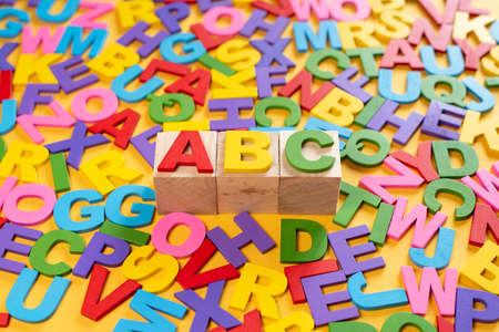Alphabet on wooden tiles and ABC on a cube against yellow background. Concept of child learning education development