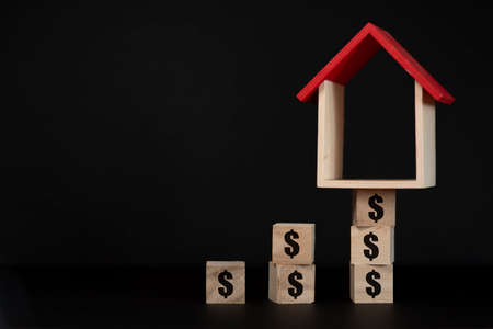 house model set on wooden cube with Dollar sign. concept of increasing house price, rent and value Stock Photo