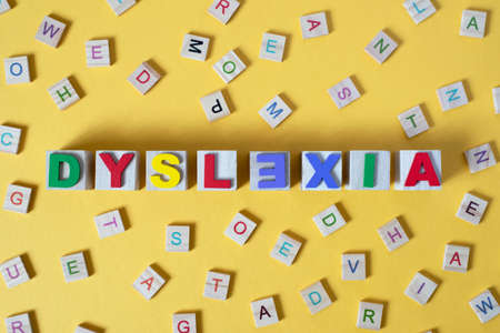 wooden alphabet blocks with DYSLEXIA word in the center on yellow background. Concept of Dyslexia awareness and human brain development