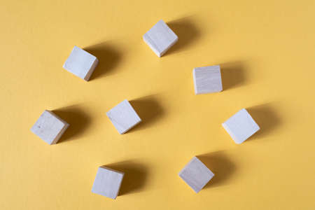 Blank wooden cube on a yellow backgorund. Concept of toys and teamwork