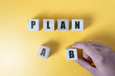 Hand choosing plan B over yellow background.  Concept of planning and strategy