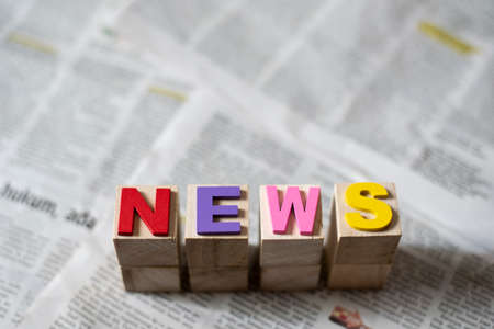 word news on a newspaper background. Concept of journalism and current issues