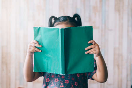 little girl with ponytail reading a book while covering her face. Concept of early education, hobby and childhood