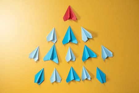 Blue paper aeroplane origami following rhe red one on yellow background. Concept of leadership, teamwork and craft