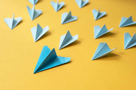 Group of blue paper aeroplane origami on yellow background. Concept of leadership, teamwork and art craft Stock Photo