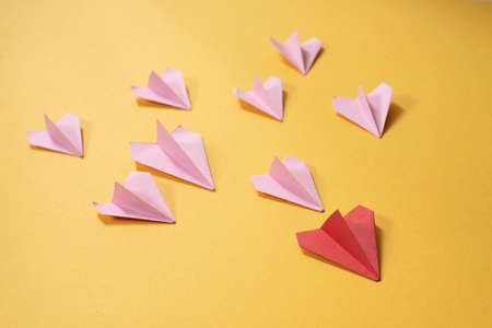 Group of pink paper aeroplane origami following the red one on yellow background. Concept of leadership, teamwork and art craft Stock Photo