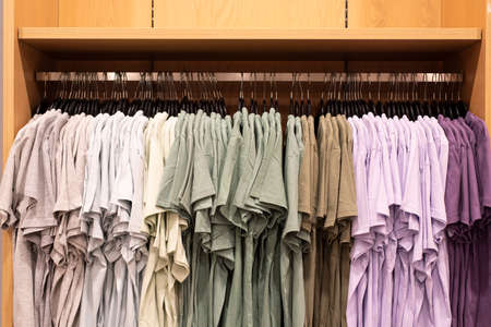 Colorful mens shirt hanging in clothing outlet display shelf. Concept of fashion, consumer and shopping Stock Photo