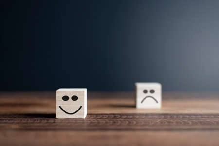 Happy and sad smiley faces on wooden blocks. Concept of Customer satisfaction or evaluation