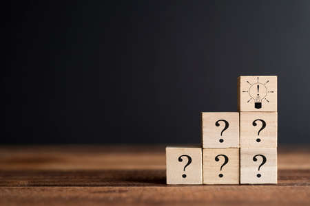Question mark and Exclamation mark bulb on a wooden cube. Concept of FAQ, Questions and answers, Brainstorming and teambuilding Stock Photo