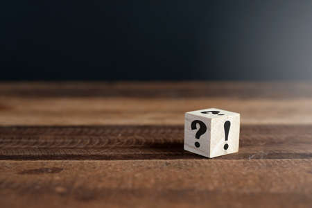 Wooden cube with question mark and exclamation point on wooden table. Concept of uncertainty, faq and questions and answers
