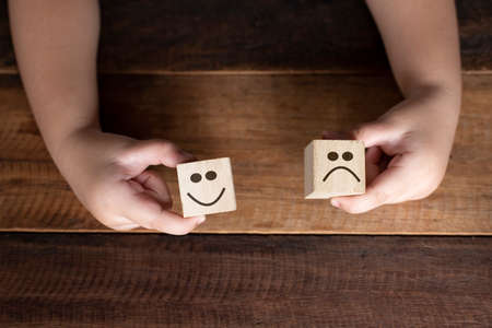 Child hand holding wooden cube with smiling face icon. Concept of Emotion,expression and rating
