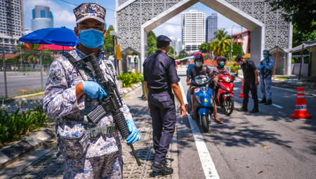 KUALA LUMPUR, MALAYSIA - APRIL 18, 2020 : Malaysia soldier officer inspect road users at a roadblock to enforce the order to stay at home, during the 'movement control order' COVID-19 outbreak.