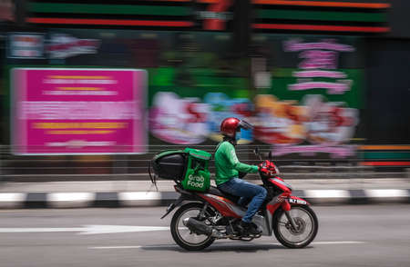 """Kuala Lumpur, Malaysia - APRIL 17, 2020 : """"GRAB FOOD"""" MOTORBIKE at the street with selective focusing and motoin blur effect. Food delivery service through its app. Editoriali"""
