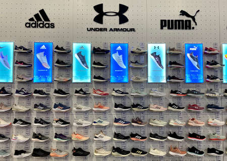 Kuala Lumpur, Malaysia - May 18, 2020 : Row of variety branded sports shoes on display in local sports outlet