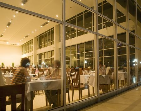The people sitting in restaurant, behind a glass wall Stock Photo