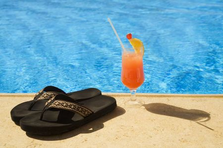 Cocktail and slippers stand on edge of pool. A maximum of rest!