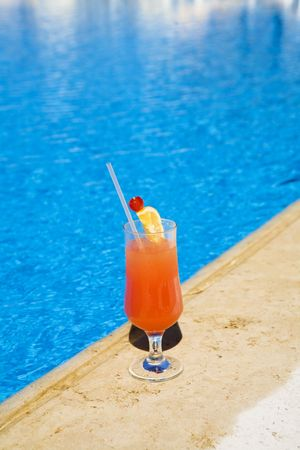 Cocktail stands on edge of pool. as a symbol of a rest. photo