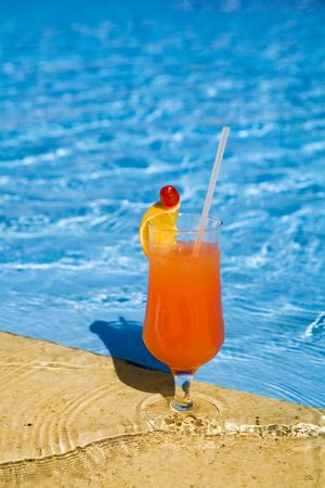 orange cocktail with lemon stands on edge of pool. photo
