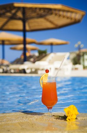 orange cocktail stands on edge of swimming-pool near a flower. Traditional resting. photo