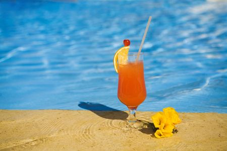 orange cocktail stands on edge of swimming-pool near a flower. photo