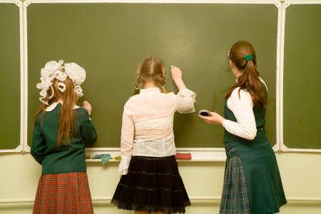 three school-friend drawing on a blackboard.