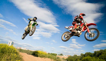 two motocross riders in the air