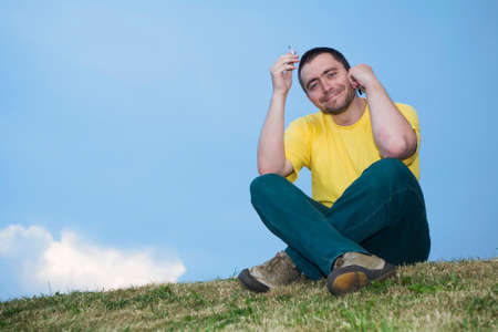 smoking man on the grass and speaking by the phone Stock Photo - 1478718