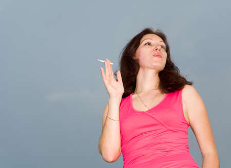 deleterious: smoking woman in scarlet clothes Stock Photo