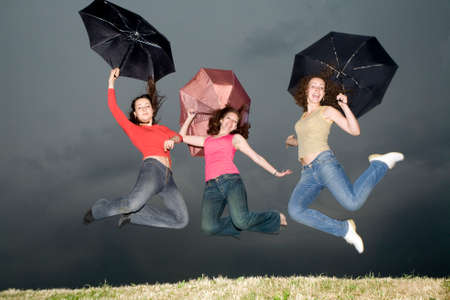 three girls with umbrellas jumping on the storm-cloud Stock Photo - 1478722