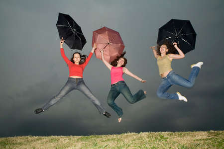 three girls with umbrellas jumping on the storm-cloud photo
