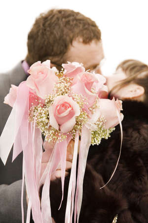 pair are kissing behind a wedding bouquet photo
