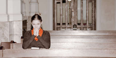 pew: girl pray in a catholic church