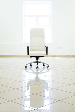 commodious: excellent white armchair in empty room