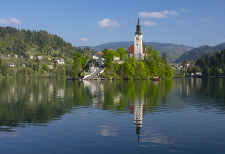 Island on Bled lake and pilgrimage church of the Assumption of Mary with mountain landscape background reflected in water at sunny day, Slovenia